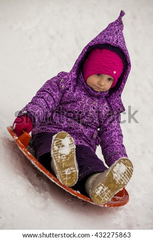 The girl rolls down snowy hill  - stock photo