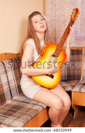 The girl sings and plays a guitar. - stock photo