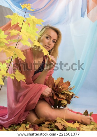 The girl sits with yellow maple leaves - stock photo