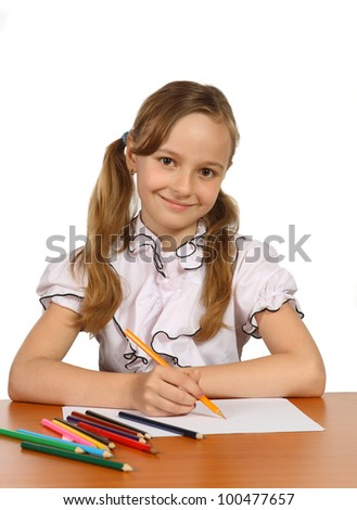 The girl, sitting at the table and make drawings on paper, on a white background - stock photo