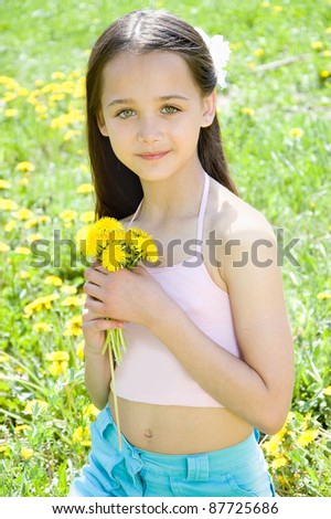 The girl sitting in the grass with dandelion in hand - stock photo