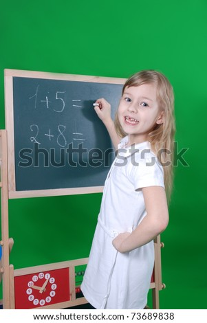 The girl solves mathematical examples at a board - stock photo