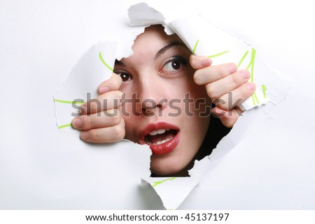 The girl spies through a hole in a paper. - stock photo