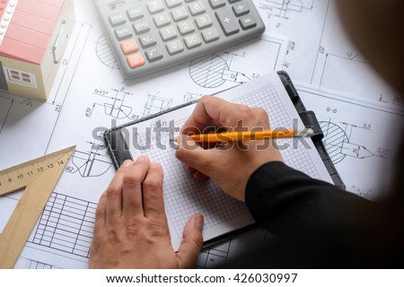 The girl the designer, architect, business woman makes calculations, drawing drawings, diagram, writes the formula on a wooden table with blueprints, toy house and calculator. With lights effects. - stock photo