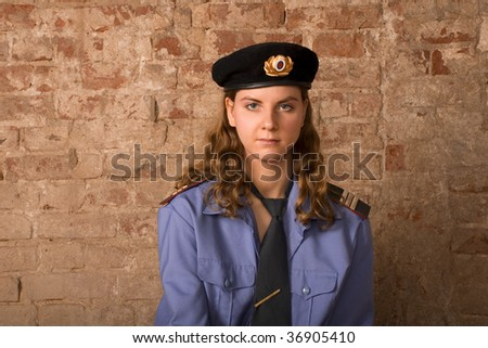 the girl the sergeant of militia against a brick wall - stock photo