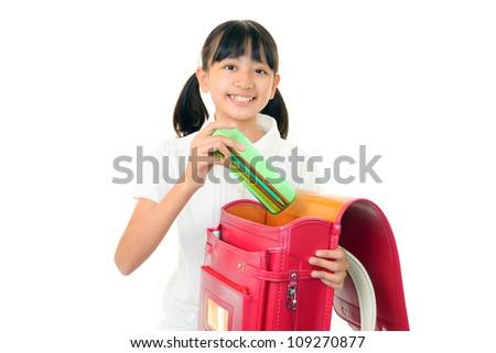 The girl who sets up the schoolchild's satchel joyfully - stock photo