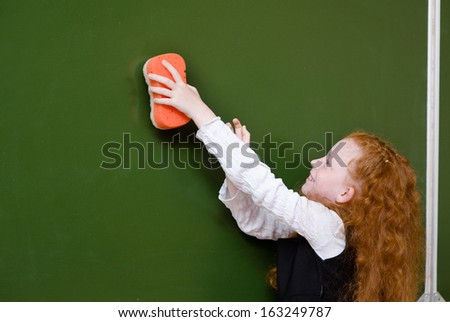 the girl wipes the chalkboard with a sponge - stock photo