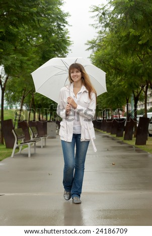 The girl with an umbrella standing under a rain - stock photo