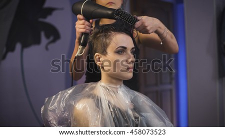 The girl with blue hair in a beauty salon. Hairdresser makes hair styling for girls punk. Powered hairdryer and comb - stock photo