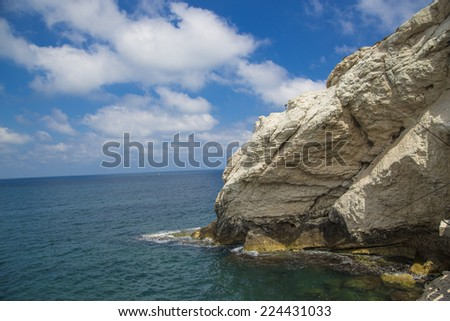 The gleaming white cliffs of Rosh Hanikra and the beautiful stretch of beach below are a magnificent sight to behold. - stock photo