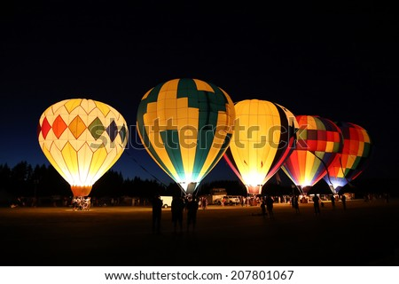 The glow of a hot air balloon at night - stock photo