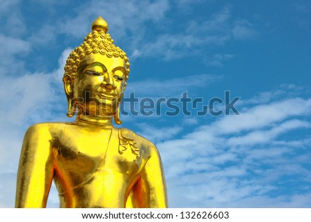 The gold buddha statue is on the sky background - stock photo