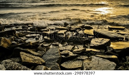 The Gold Coast. Rocky Lake Michigan shore at sunset. - stock photo