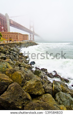 The Golden Gate Bridge runs over Fort Point and disappears into the fog on a typical San Francisco day. - stock photo