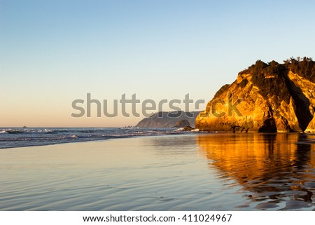 The golden hour sunset along the Pacific Cost At Hug Point State Park, Oregon. - stock photo