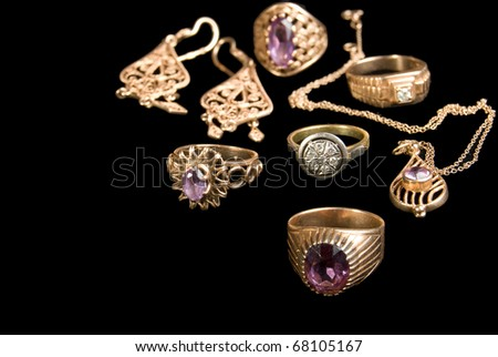 The Golden jewelries, is isolated on a black background - stock photo