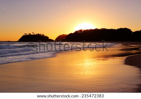 The golden sun rises behind the headland and detached island at Number One Beach, Seal Rocks NSW Australia.  The beach is 1.3km long and curves around to face  - stock photo