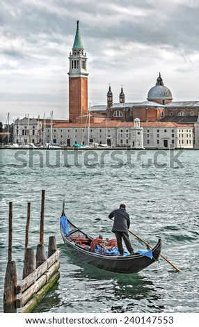 the gondolier and the bell tower of the Saint Giorgio Maggiore Church on background (view from San Marco embankment) - Venice, Italy - stock photo