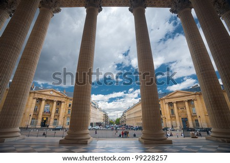 The grand columns of the Pantheon and neighboring Parisian buildings are uniquely seen from the inside looking out point of view in Paris, France. - stock photo