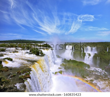 The grand Iguazu Falls on the Brazilian side. Multi-tiered cascades of water roar of lush jungle. Over boiling water swirls fine mist - stock photo