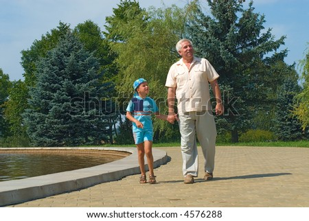 The grandfather and grandson walk in park - stock photo