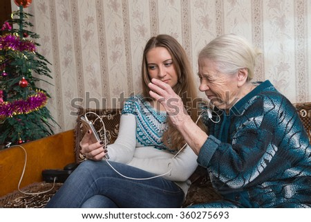 the grandmother and the granddaughter talk by video conference to relatives  - stock photo