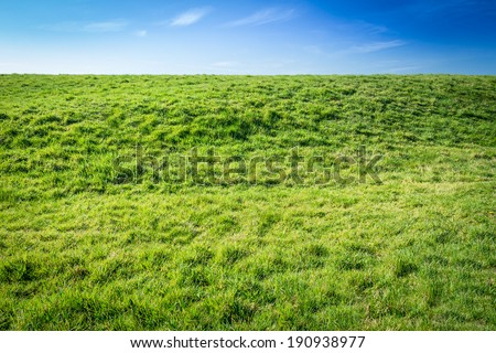 The Grass is always greener - Green grassy damm with blue sky - stock photo