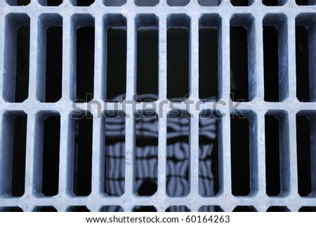 The grate of manhole cover on the roadside - stock photo