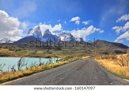 The gravel road along the shore of Lake Pehoe. The National Park Torres del Paine in Chile. In the distance are seen cliffs of Los Cuernos - stock photo