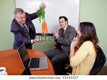 The great motivator dangling carrots and Business team motivated by positive presenter, Clapping employees - stock photo