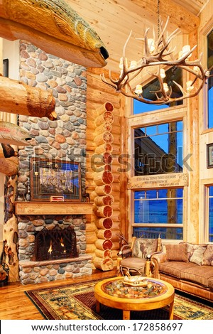The great room in a modern log cabin, with rustic decor, and furniture.. - stock photo