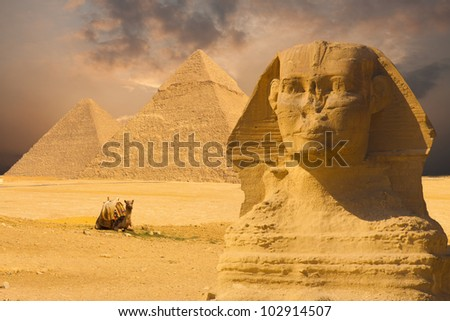 The Great Sphinx face with a set of pyramids in the background and a beautiful purple sunset sky day in Giza, Cairo, Egypt. Horizontal copy space - stock photo