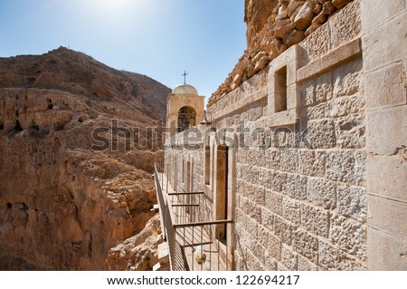 The Greek Orthodox Monastery of the Temptation perches on a desert mountain cliff overlooking the West Bank town of Jericho. - stock photo