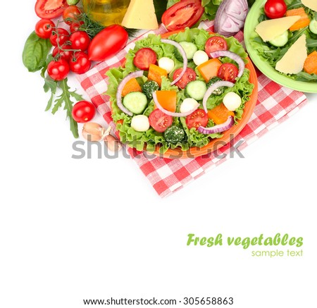 The Greek salad with cheese balls on an orange plate on a red checkered napkin and fresh ripe vegetables and herbs on a white background with a place for the text. Top view. - stock photo