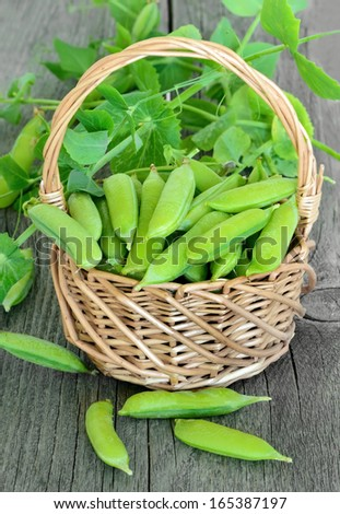 The green peas in basket on wooden table - stock photo