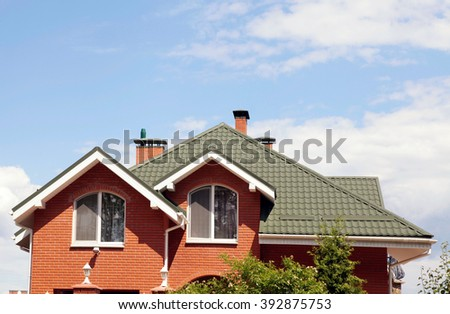 the green roof of the beautiful house with nice window and blue sky - stock photo