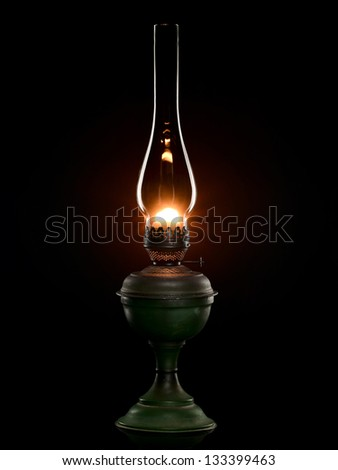 The green shone antiquarian oil lamp is isolated on the black. - stock photo