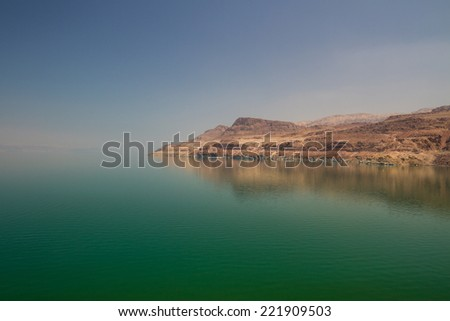The green water of the land-locked Dead Sea in Jordan, by the entrance to Wadi Mujib, on the Jordan side. The Israeli coast in the distance. - stock photo