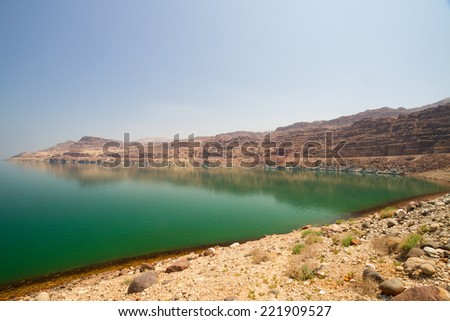 The green water of the land-locked Dead Sea in Jordan, by the entrance to Wadi Mujib, on the Jordan side. - stock photo