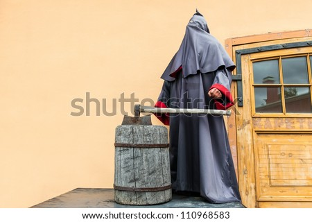 The grim reaper and executioner standing with a large axe on yellow wall - stock photo