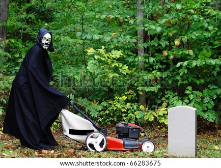 The Grim reaper mowing the grass along the woods in the graveyard with room for your text' - stock photo
