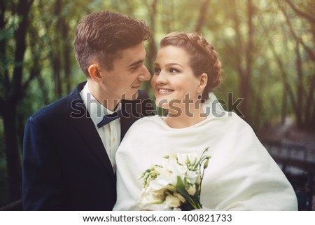 The groom and bride are walking in the park at their wedding day. Couple is looking each to other. Bride is smiling, she happy. Newlyweds in love. They became husband and wife this day. - stock photo