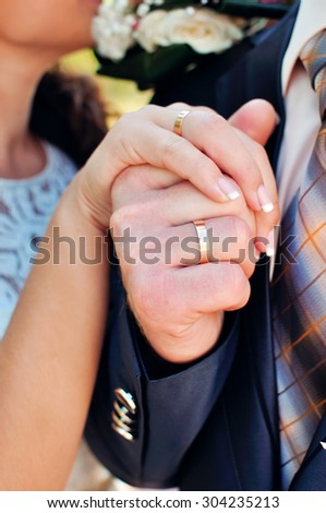 The groom and the bride hold hands. On fingers wedding rings. - stock photo