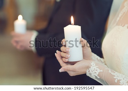 The groom and the bride with candles. Wedding ceremony in church - stock photo