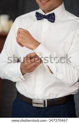 the groom dresses cuff links in wedding day - stock photo