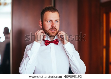 The groom in white shirt put his bow-tie in the morning of the wedding day. Close up photography. Preparation time - stock photo