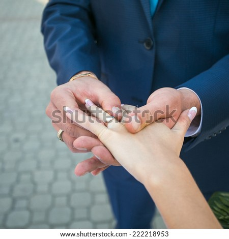 The groom puts on a ring to the bride hand. outdoor shot, daylight - stock photo
