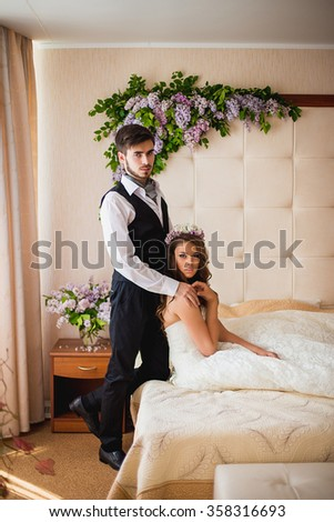the groom with the bride sit on a bed. Nearby there are a lot of flowers of a lilac - stock photo