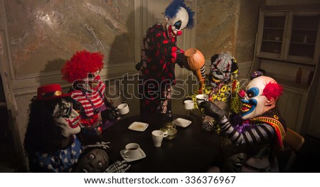 The group of clowns drinking tea at the table. Horror Halloween. - stock photo