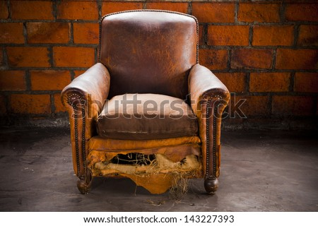 The grunge old armchair with top hi-light over the brick wall - stock photo